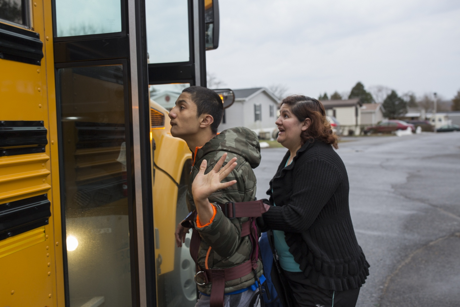 Veronica Castro helps her son Juan Pablo get in the school bus. Juan Pablo has brain damage resulting from complications during a heart surgery when he was three years old, has problems controlling his movements and has to use a harness during the bus ride.