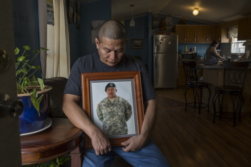 Army veteran Ricardo Pineda shows a photograph of himself when he was enlisted and wearing his military uniform while his wife Veronica washes dishes in the kitchen area of their mobile home.