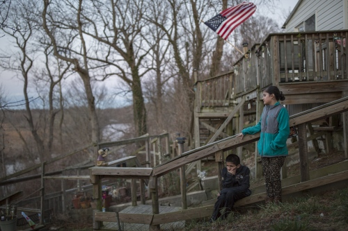 Kevin Pineda and his sister Emily stand in the backyard of their mobile home next to their neighbors' deck. The siblings were born and raised in the United States and have never been to Mexico.