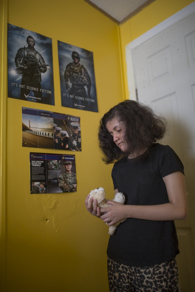 Emily Pineda, 11, in her bedroom. Emily wants to join the Airforce when she is 18 and has military posters on the walls of her room.