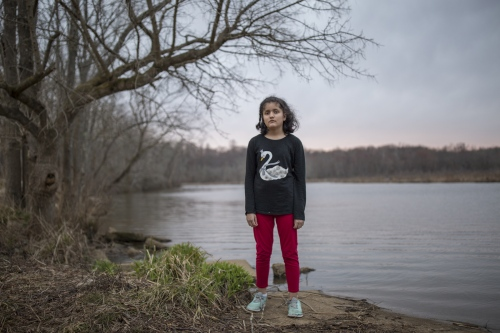 Emily Pineda, 11, stands next to a lake close to her home.