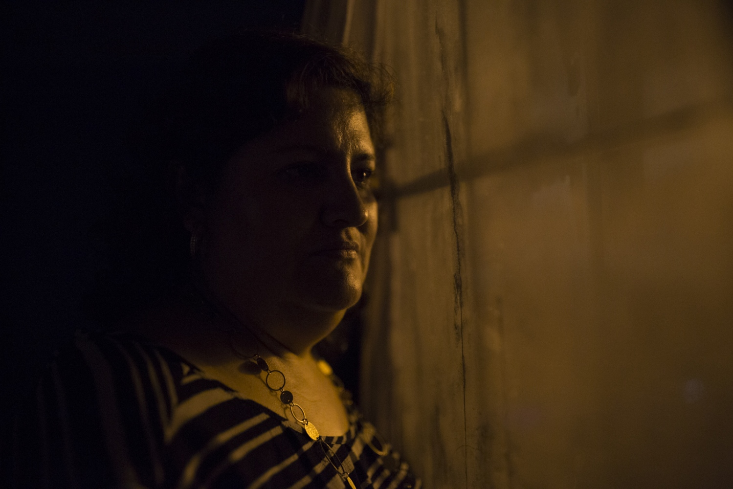 Veronica Castro looks outside through a window from her mobile home in Lothian, MD. Veronica has a temporary work permit that allows her to stay in the country but has to go through immigration check-ups periodically and is always fearing a possible deportation.