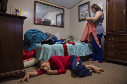 Juan Pablo Pineda lays on the floor while his mother Veronica Castro folds some clothes in her bedroom on February 8, 2017, in Lothian, MD. Juan Pablo has brain damage resulting from complications during a heart surgery when he was three years old and has been dependant on his mother ever since.