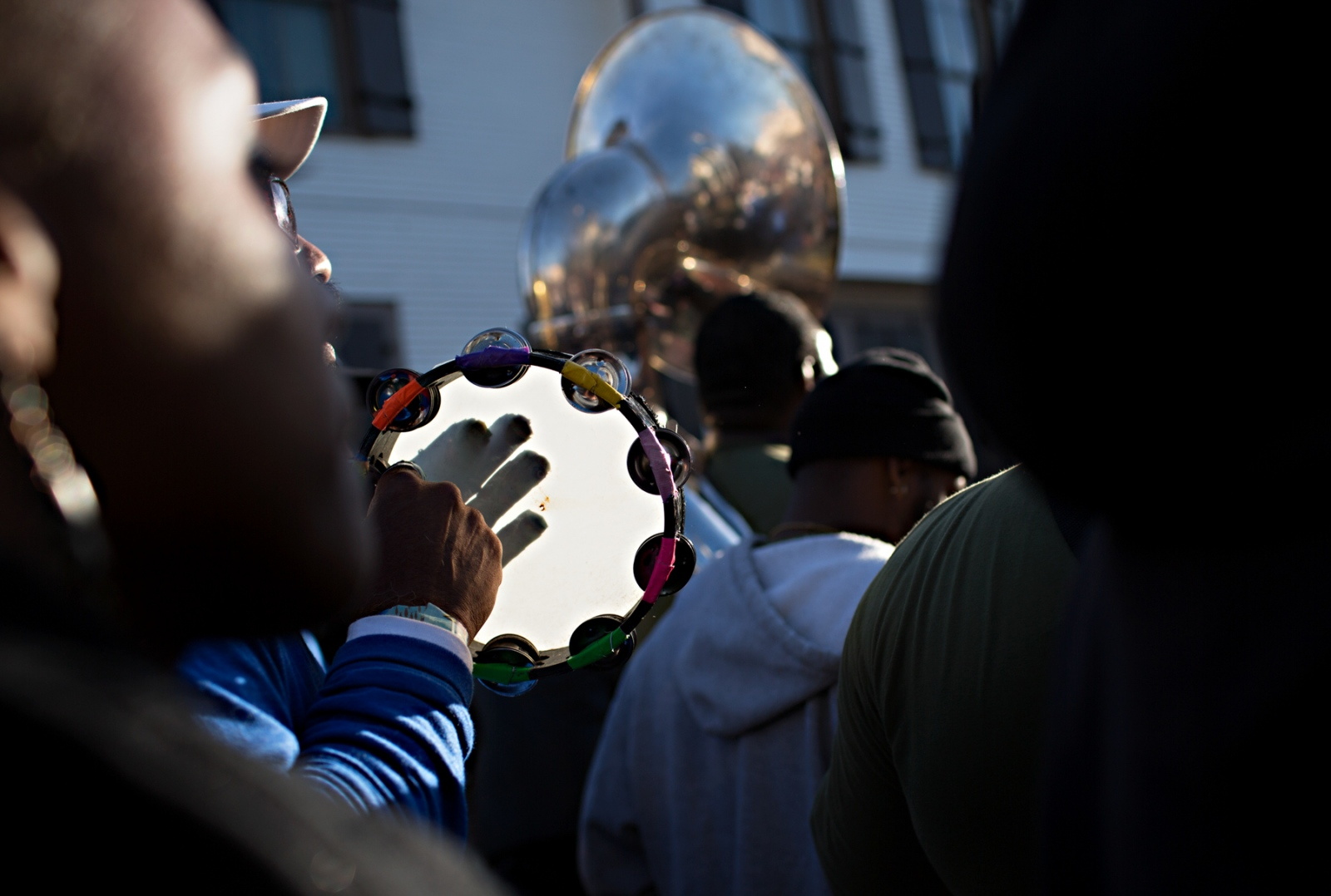 A tambourine player member of a brass band plays along under the afternoon sun during a Second Line Parade.