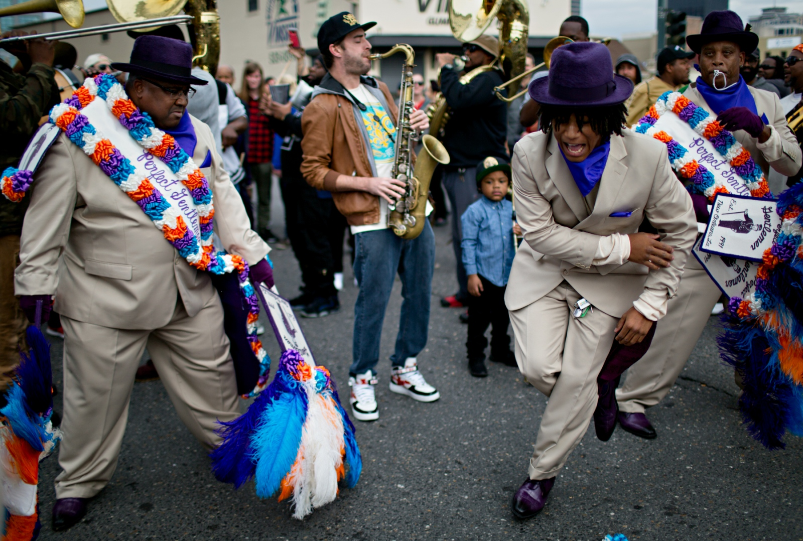 The President of the Perfect Gentleman's Social and Pleasure Club, Travis Lyons (left), looks on while his son, the rapper T. Lyons shows off his moves during the Second Line Parade. Travis Lyons has been participating and sponsoring Second Line parades for decades and essentially finances the cost of the sponsorship of his parades out of his own pocket. The cost of putting on a parade which includes all permits, police permits, costumes and all other incidental costs can go as high as $12,000 per parade.