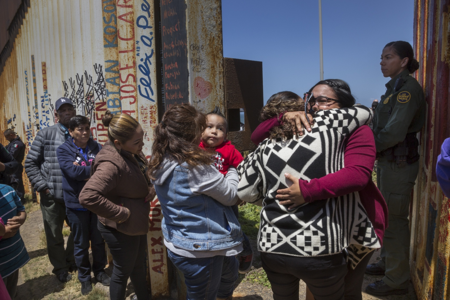 """Gabriela Esparza (in red) reunites briefly (3 minutes) with her sister Susana and her mother María del Carmen Flores during the """"Opening the Door of Hope"""" event at the border wall in Playas de Tijuana, Mexico, on April 30, 2016. On January 2018, Border Patrol announced the door will not re-open this year."""