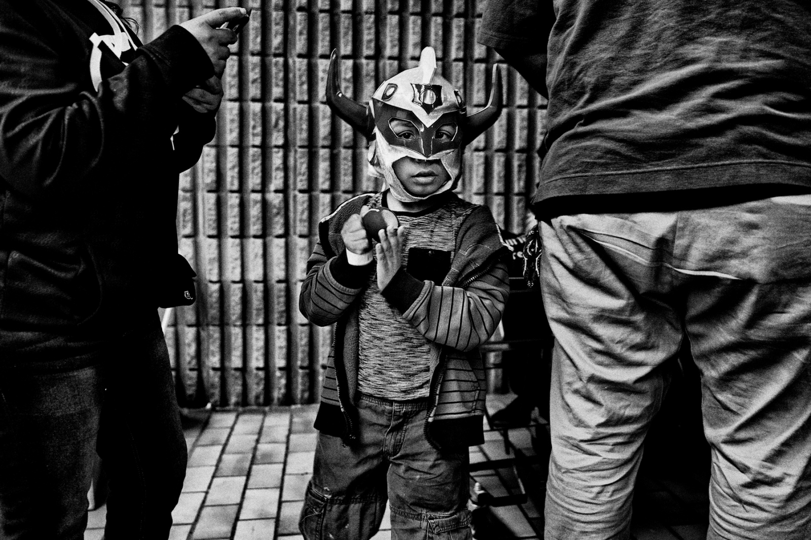 Young Angel is wearing the mask of his super hero during an intermission where luchadores get to meet and greet and sign autographs for their fans.