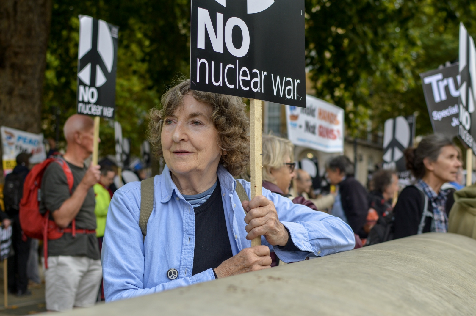 An old lady holds a sign during a peaceful march against nuclear weapons held in front of Downing Street, London, April 2018