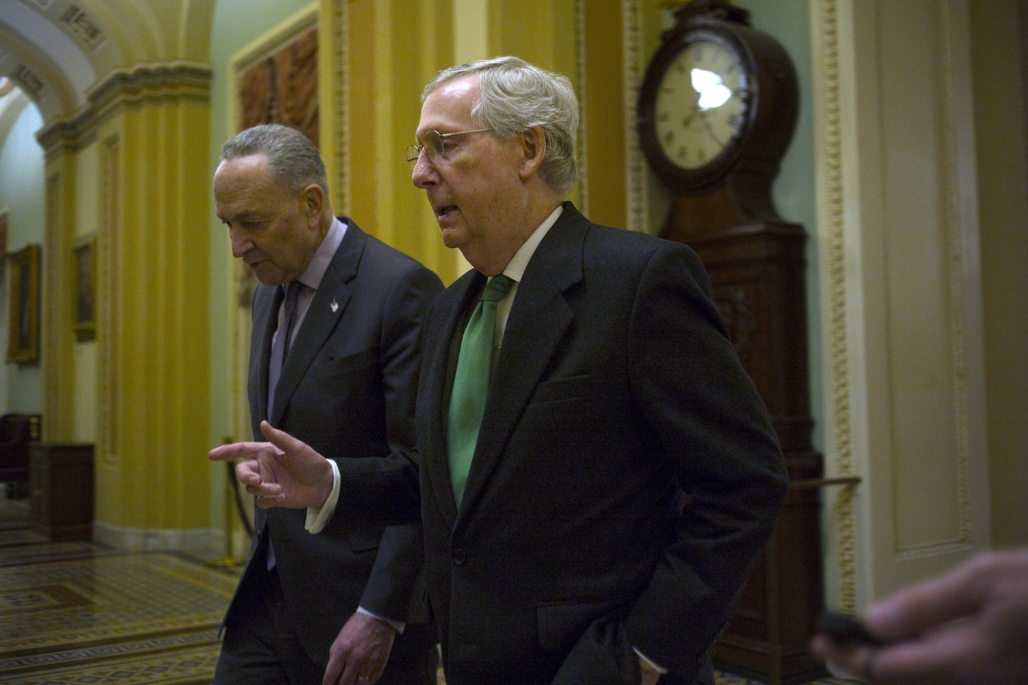 Senators Mitch McConnell and Chuck Schumer discuss the deal that will end the government shutdown as they walk into the Senate Chamber.