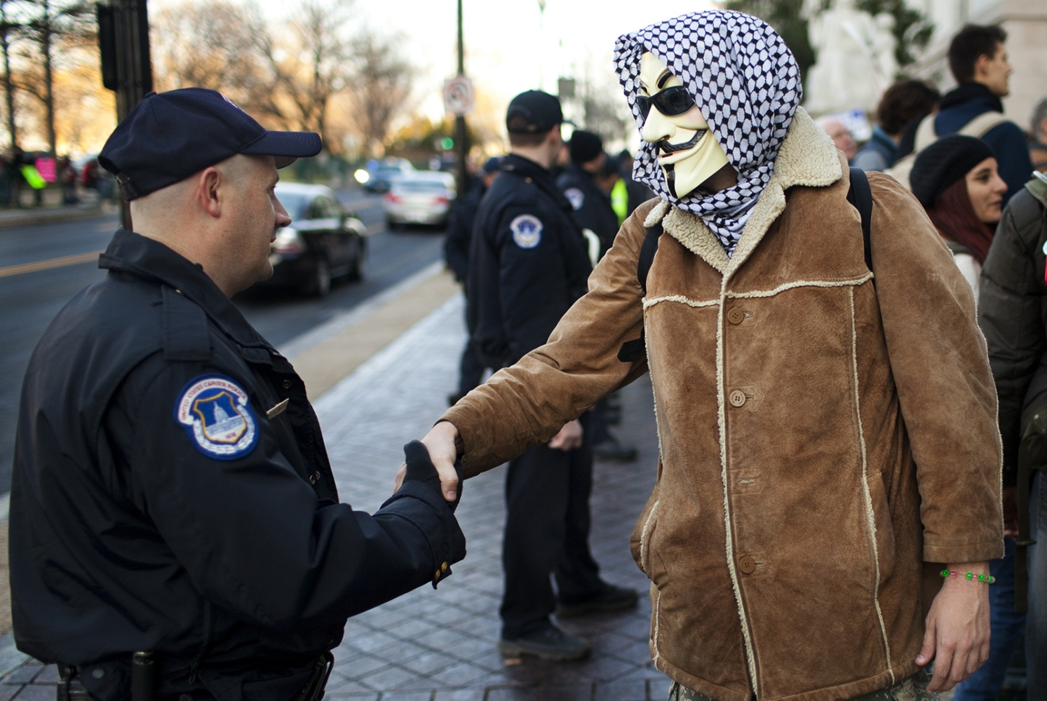 An officer of the Capitol Police shakes hands with an Occupy protest on Capitol Hill.