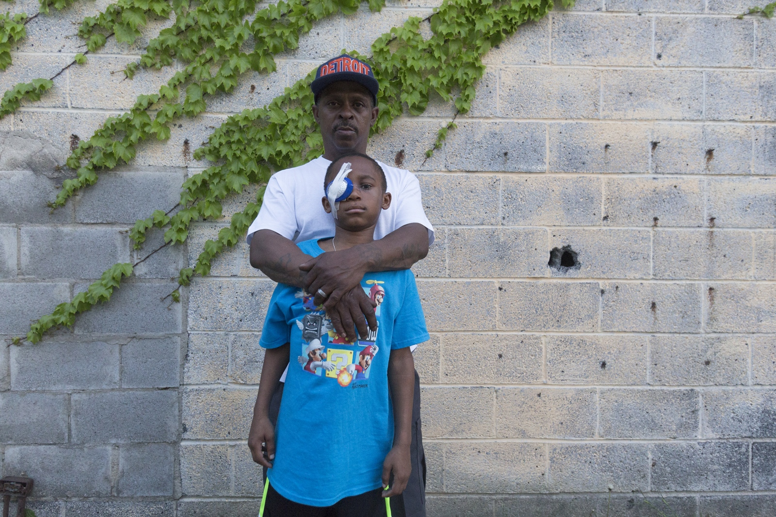 Cecil Cosey holds his son Malik Cosey, 9, on Wednesday, May 17, 2017, in Detroit. Malik was shot in the head while waiting in the car to go see the movie Boss Baby with his family in early April.