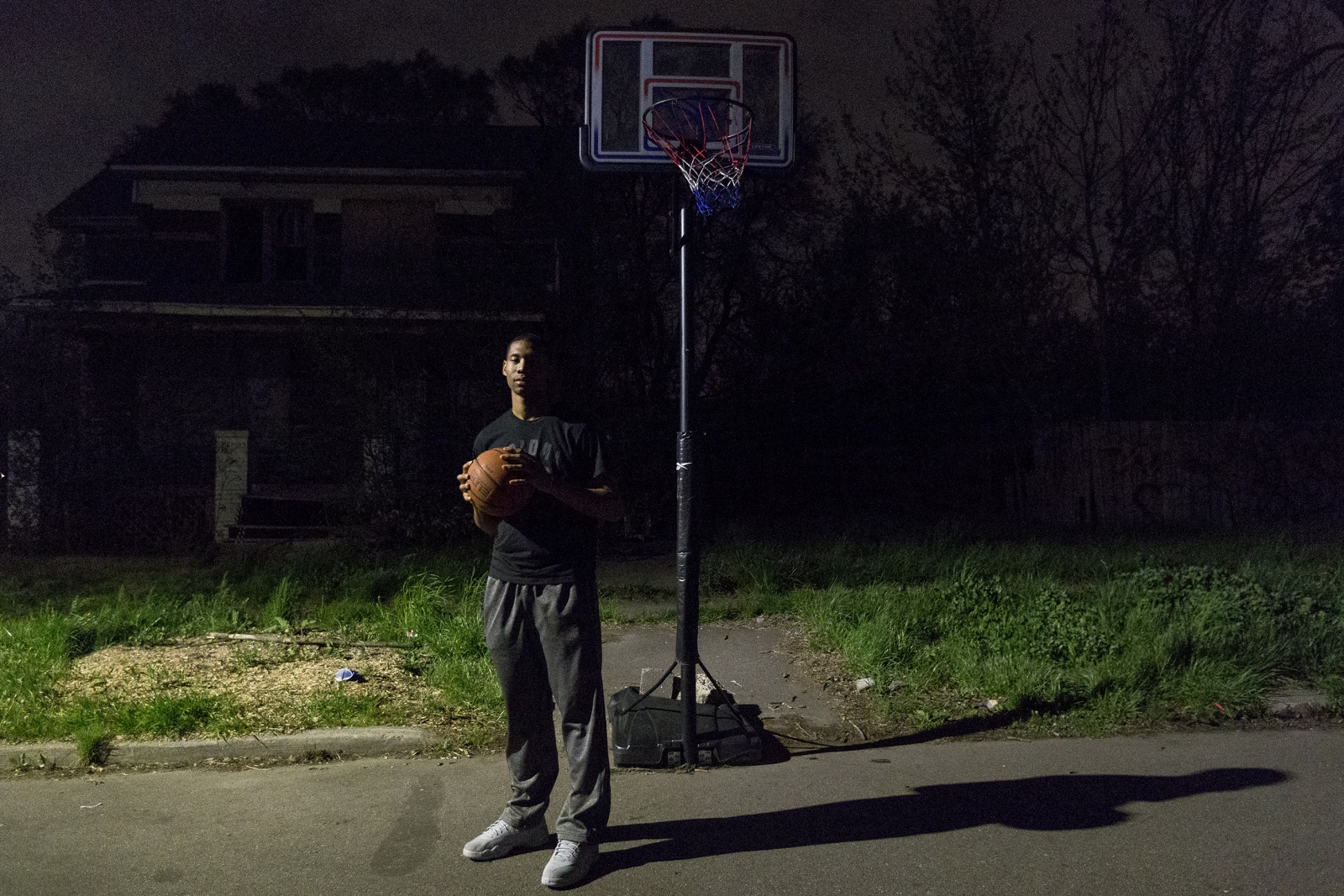 Michael Green, 17, stands under the same basketball hoop he was shot at when he was only 12 years old, down the street from his home in Detroit. Michael accepted a scholarship to play basketball at Miles College in Alabama for fall 2018.