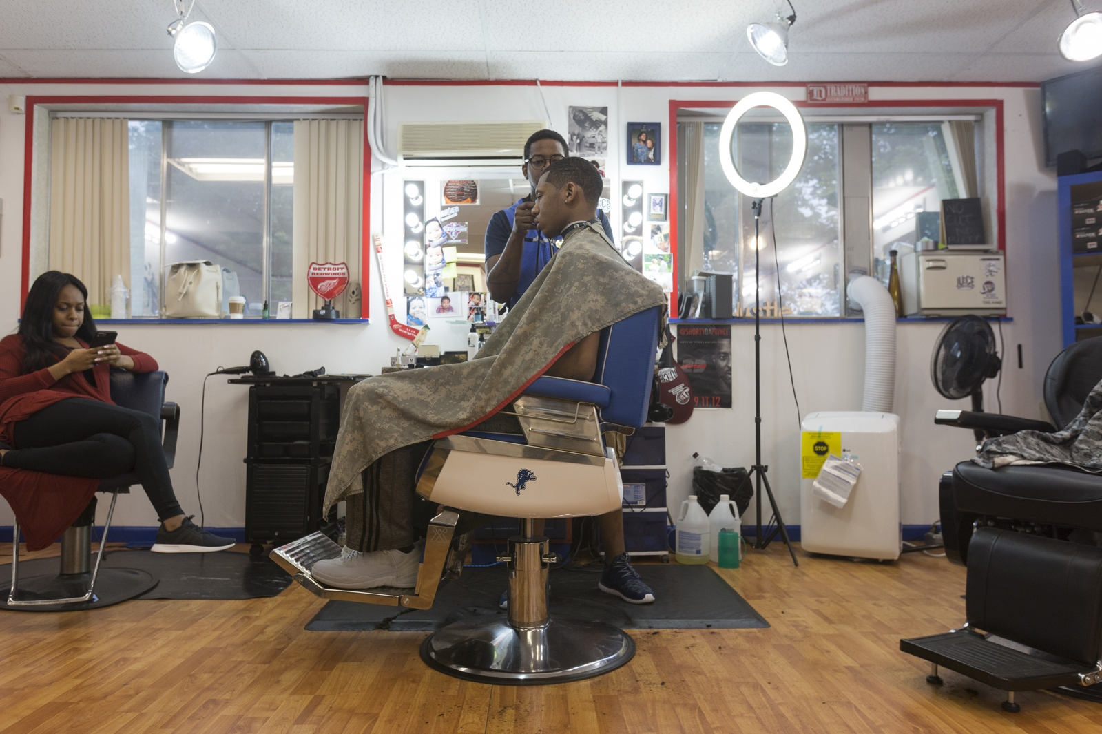 "Garret ""Tha Barber,"" trims Michael Green's hair on Friday, May 19, 2017 in his Southfield barber shop."
