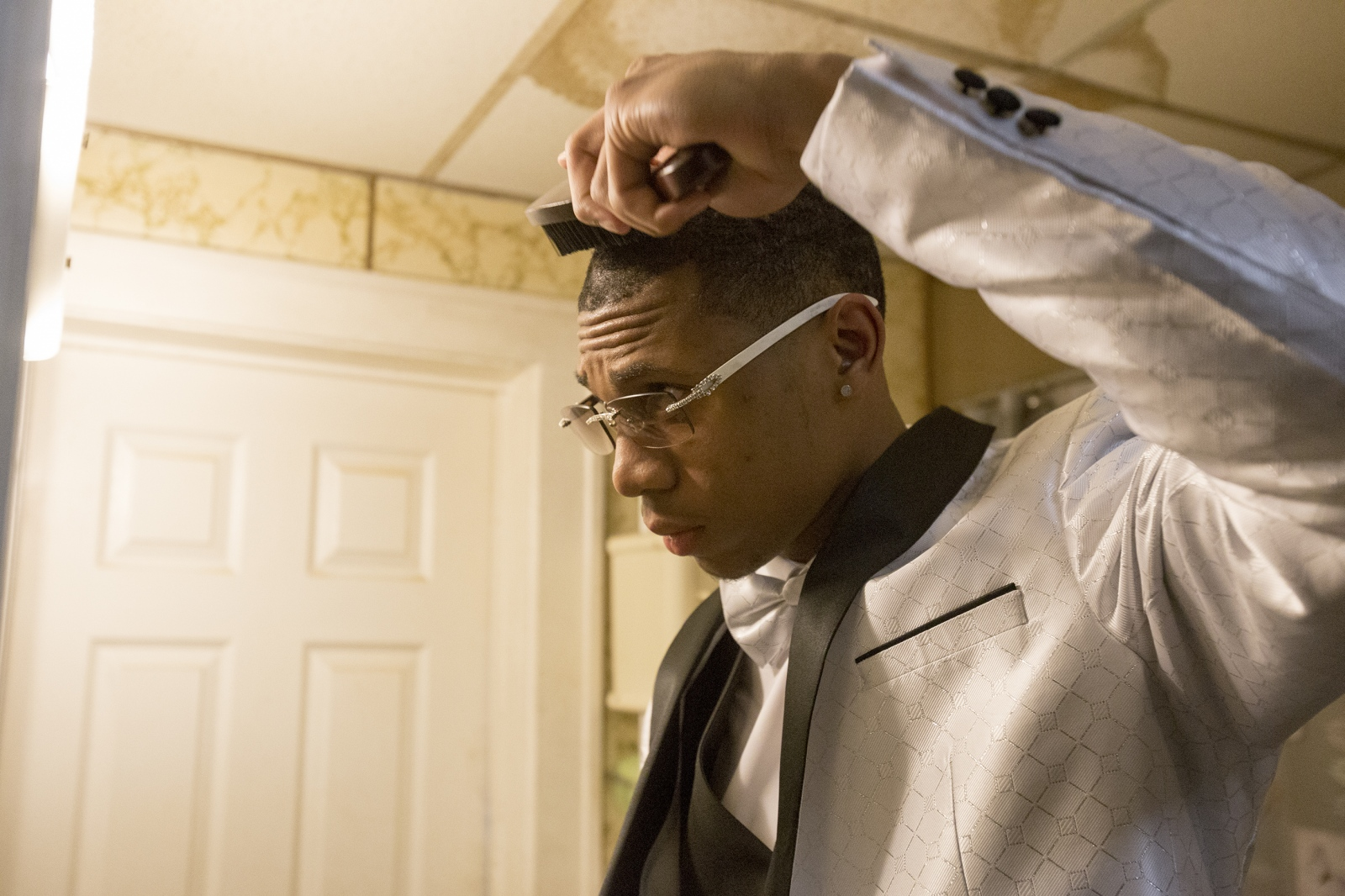 Dressed and nearly ready, Michael brushes his hair in his bathroom before he leaves for his senior prom in Detroit.