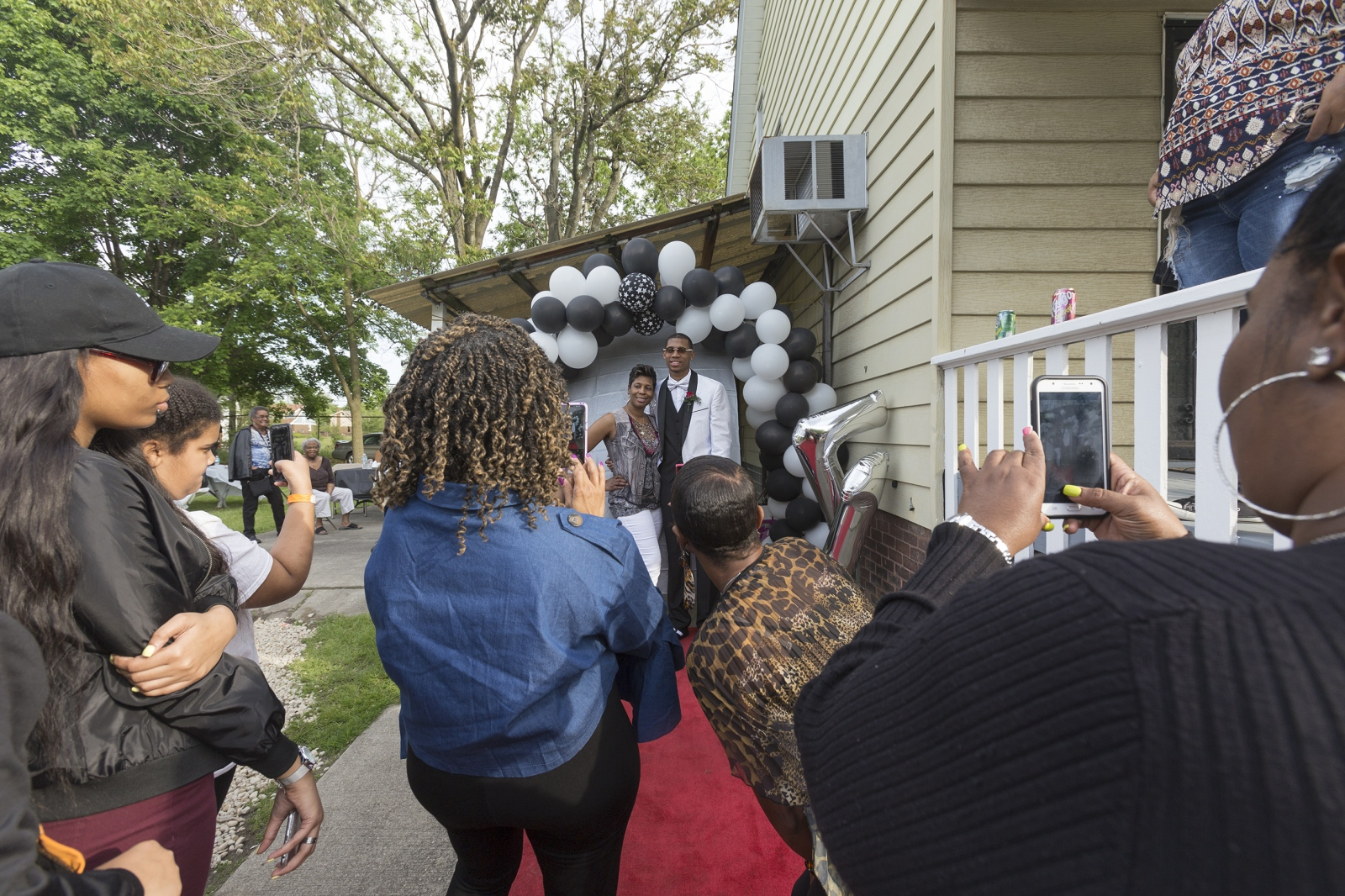 LaShaunda Forrest, left, and her son Michael Green pose for photographs before he leaves for prom. LaShaunda invited friends, neighbors, and family over to eat dinner and celebrate this milestone in Michael's life. Michael will graduate from Cass Technical High School in a couple of weeks and head to Miles College in Alabama on a basketball scholarship.