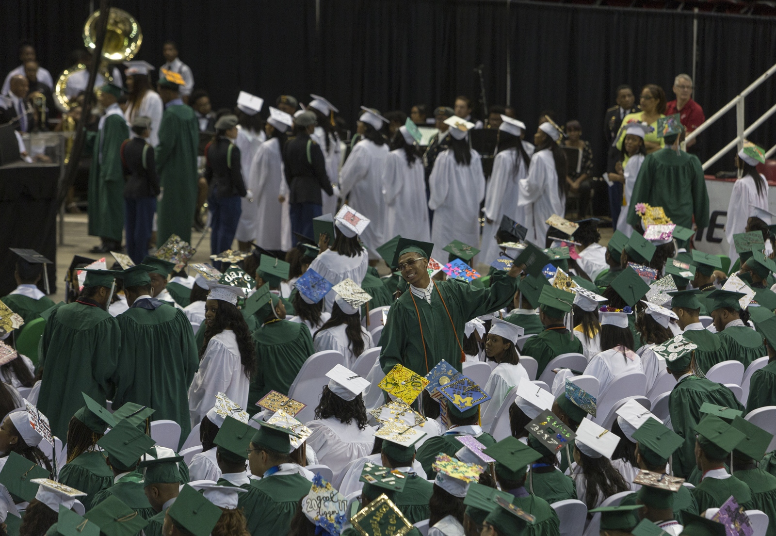 Michael Green, 18, holding his diploma, turns toward the crowd looking for his mother and grandmother, after walking across the stage during his high school graduation at Joe Louis Arena in Detroit.