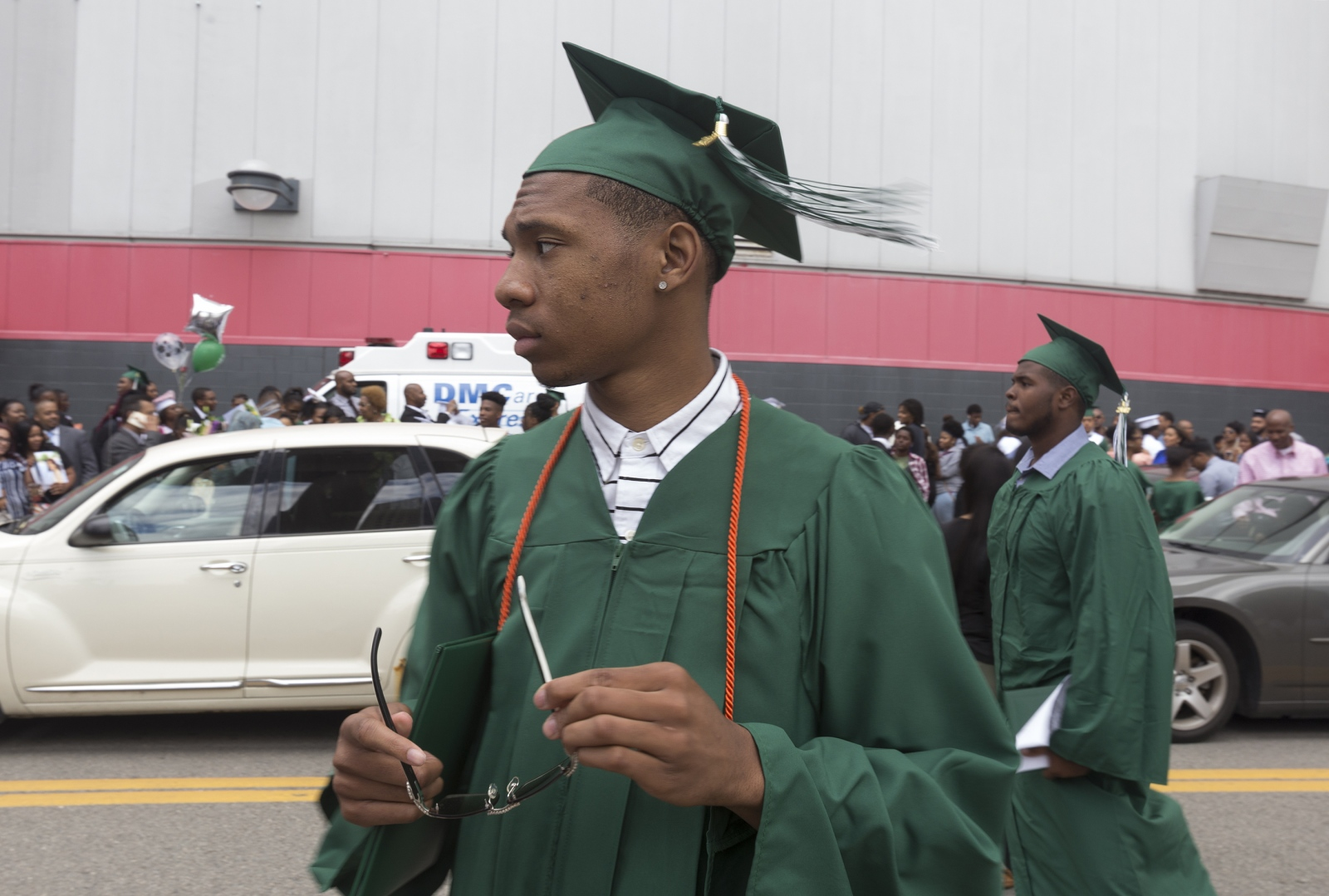 Michael Green, 18, looks for family and friends after his high school graduation ceremony outside Joe Louis Arena in Detroit.  Five years after being an unintended victim of a gunshot, Michael will be heading to Miles College in Alabama on a basketball scholarship.