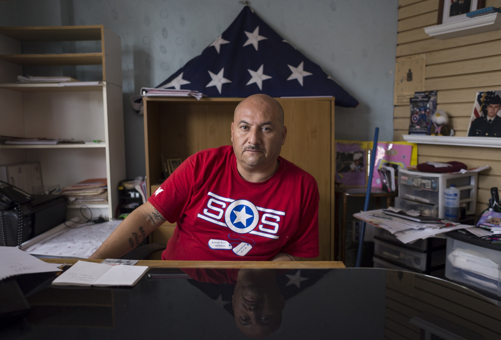 Deported Army veteran Hector Barajas, 38, sits at his desk at the Deported Veterans Support House, where he lives and works. The mission of the Support House is to find and provide help to deported veterans around the world.