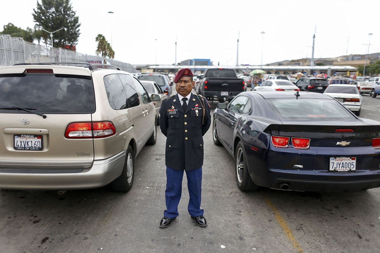Fabian Rebolledo, 38, a deported U.S. paratrooper, poses in his military uniform along the Mexico-U.S. border crossing, moments after he was denied entry into the U.S. Rebolledo was deported in 2010 for check fraud; he recently won his fight to have his felony reduced to a misdemeanor, no longer a deportable offense, but has still not been allowed back into the United States.