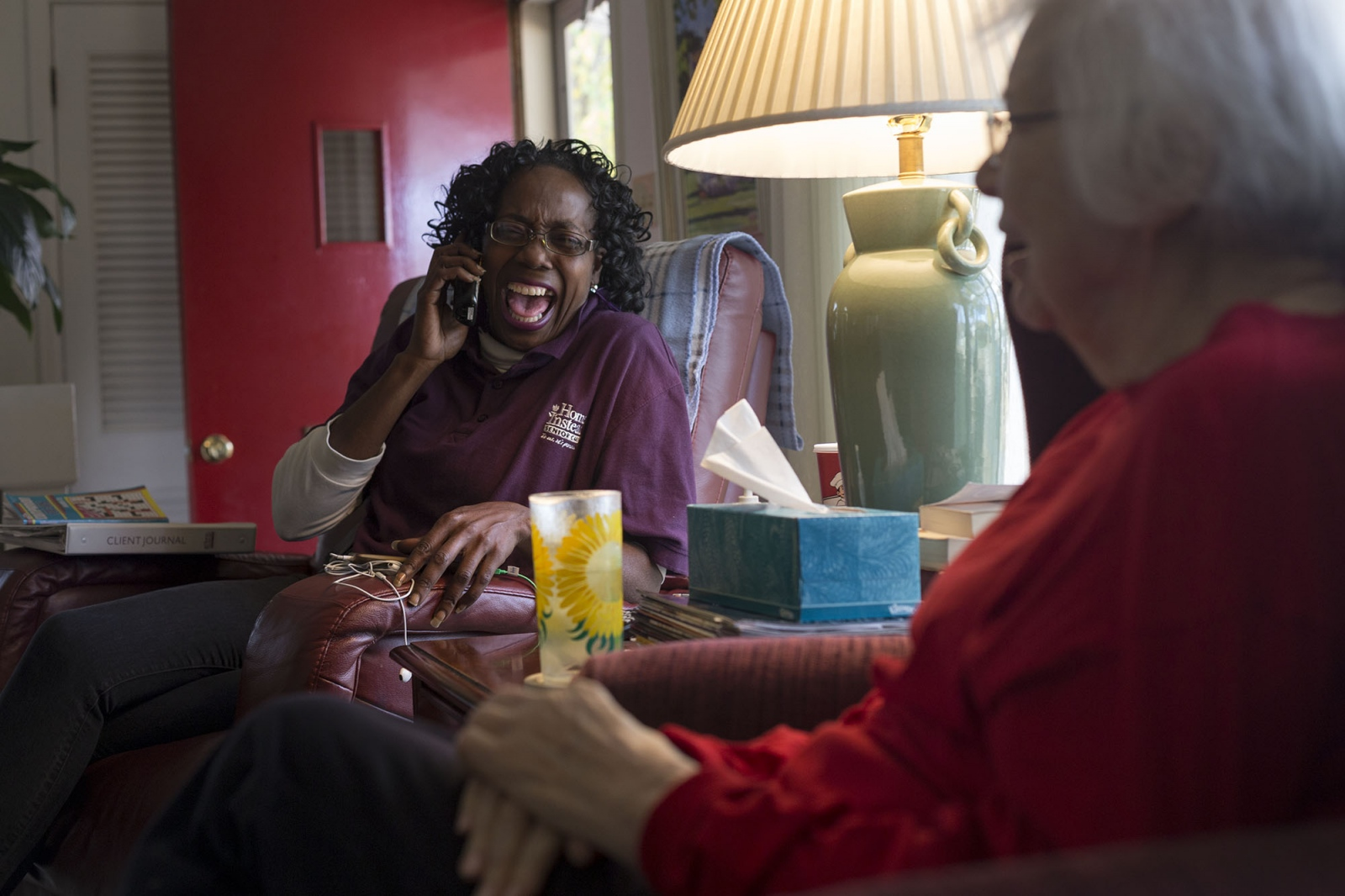 Jackie Lloyd, left, laughs over the phone while Lois Jones watches television on Wednesday afternoon, Nov. 9 at her home in Royal Oak, Mi. Lloyd has been working with Jones a little over two years as a caretaker with Home Instead Senior Care.