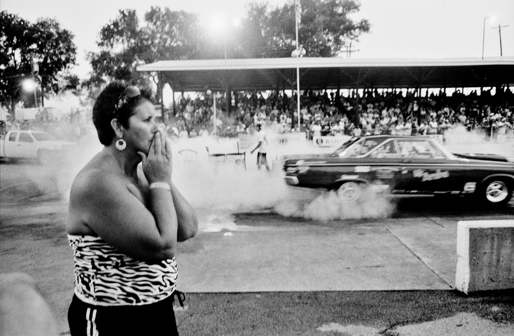 She could hardly watch as her husband smoked the tires and lurched down the track in his souped-up hot rod. It was over in seconds but took a lifetime, classic American drag-racing event Bowling Green, Kentucky.