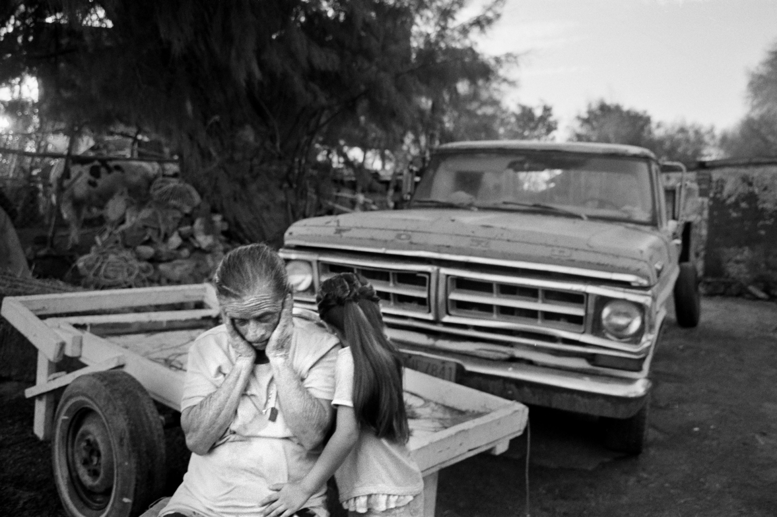 Sitting on her family's failing farm, a grandmother is comforted by her daughter in Sonora, Mexico. The farm, with its thin cows and now arid land, sits only yards from where the Colorado River once provided life.