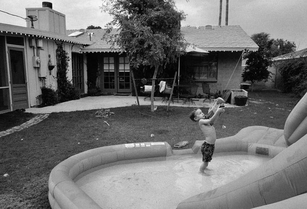 A child plays alone in his suburban backyard near Phoenix, Arizona.