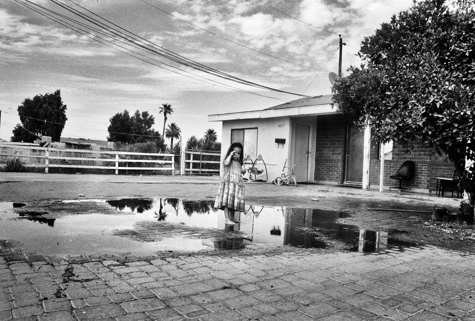 A young girl stands and cries in the desert heat of Arizona after her being hosed down with water in their front yard near Phoenix. The family could not afford air conditioning, so improvised the best they could to keep cool.