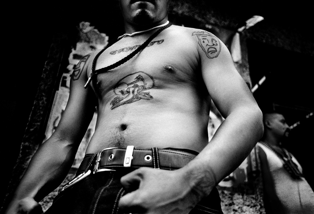 Gang members and dealers line the streets of Tepito, Mexico City's toughest neighborhood. Each tear coming from a gang member's tattoo represents a murder committed. Tepito is controlled by drug cartels, and access to the neighborhood is strictly guarded. Police are only allowed to patrol its streets 2 days a week.
