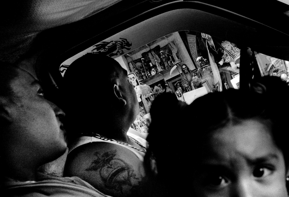 """""""Gerardo"""" takes his family to view one of the many other Saint Death altars that has popped up outside of Tepito, in other poor Mexico City barrios."""
