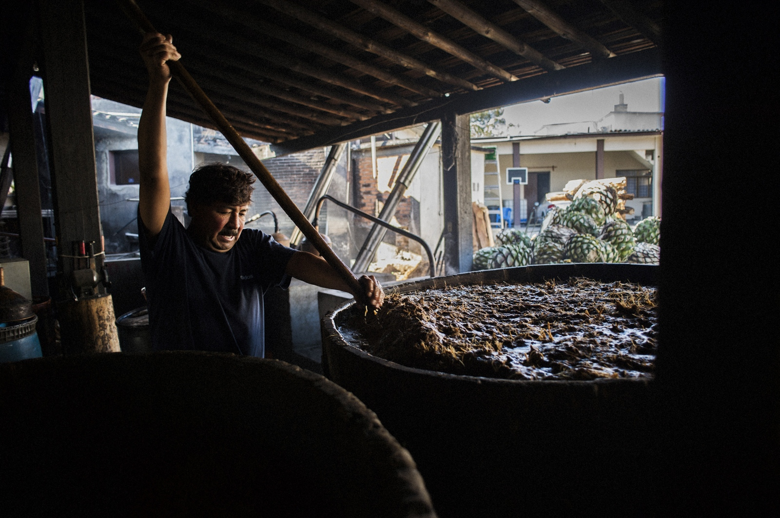 Master mezcalero Octavio Jiménez Monterroza stirs the agave mash, which will be fermented in wooden barrels for three to ten days before the juice is then separated out and distilled. The art of producing mezcal was passed down to Octavio from his father, Don Isaac, whose name adorns the family label.