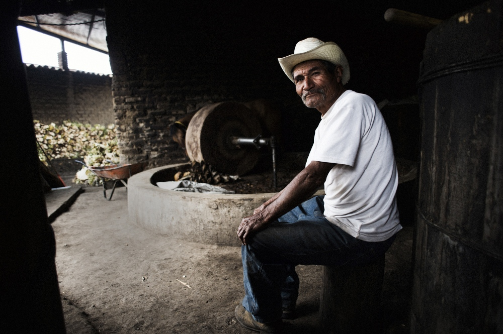 A mezcalero sits in front of the large stone wheel used to break down agave into a pulp.