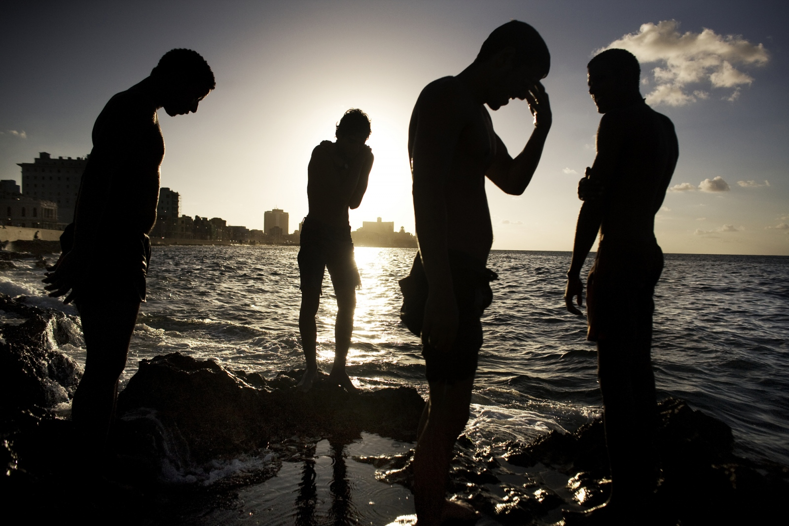 A group of Cuban young men take a break from swimming in the water in front of the Malecon sea wall in Havana, Cuba.