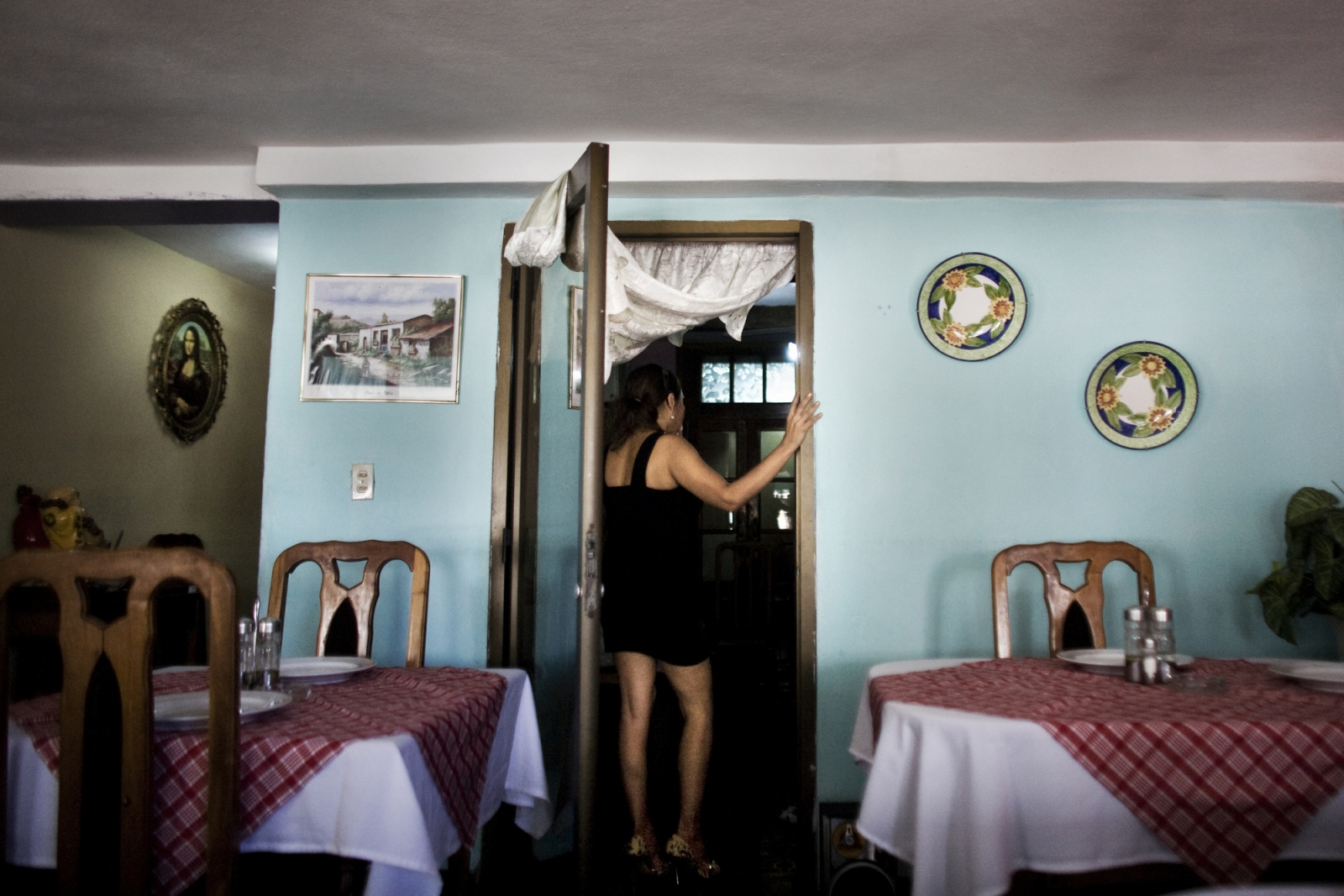 A restaurant owner in the dining room of her small, privately owned restaurant in Havana, Cuba. The relatively few private restaurants are allowed to have a maximum of twelve seats for customers and must buy their food from state owned markets, in addition to being heavily taxed.