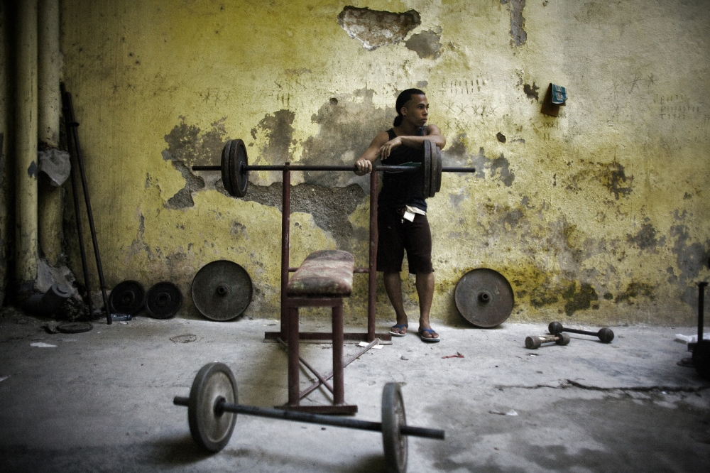 A small makeshift gymnasium housed in the bowels of a large apartment structure in Havana, Cuba. People have improvised and come together to create shared spaces such as this, in the absence of privately owned gymnasiums.