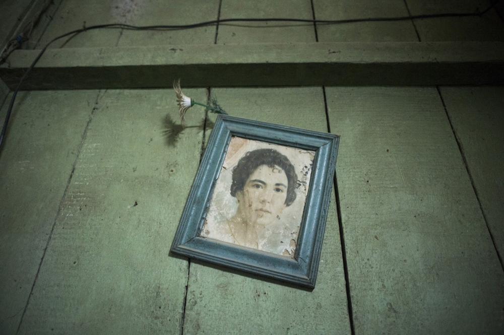 An old photo hang on the wall of Hector Gutierrez, a former sugar cane worker who now occupies one of the last standing, original colonial homes a sugar baron's family in Senado, Cuba