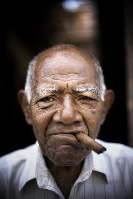 A man sits with his Cuban cigar in Havana Vieja, Cuba.