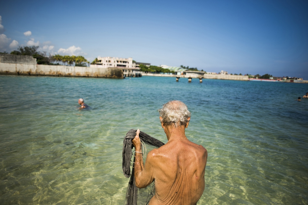 A man fishes with an old, traditional fishing net behind the Havana Yacht Club.