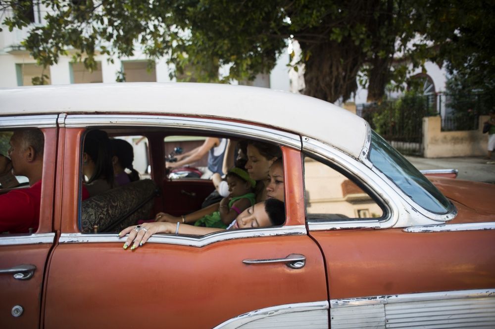A family rides in a communal taxi in the Miramar neighborhood outside of Havana. Known as an almendrone, the taxis are typically 1950's American cars travelling on fixed routes in and around Havana, providing cheap transportation to Cuban nationals.