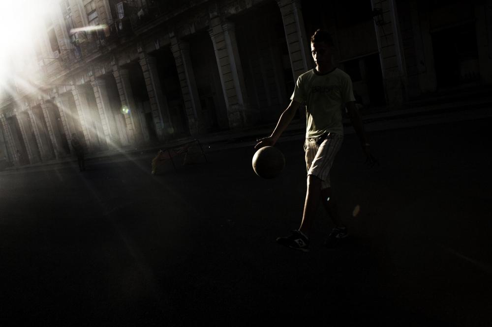 Teens play soccer on the streets of Havana, Cuba.