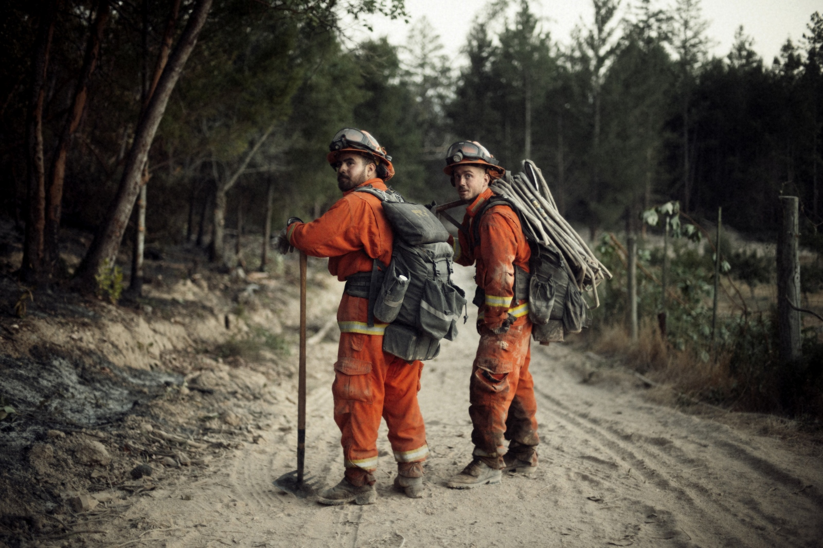 Inmate firefighters from the Antelope fire crew take a breather while carrying gear off of a burning hill during the wine country fires.