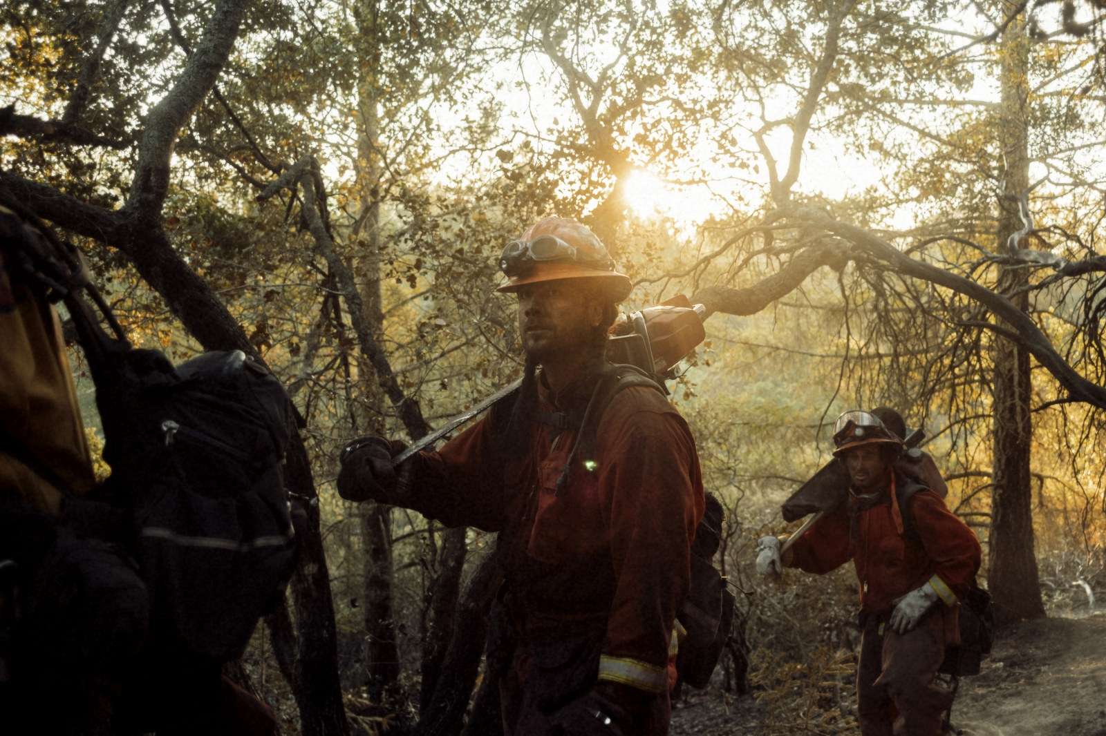 The Antelope fire crew marches into action in Sonoma, CA during the wine country fires that devastated the region. Much of an inmate fire crew's work is done by cutting lines into burning brush with power tools so that water lines can then be brought in to put out fire.
