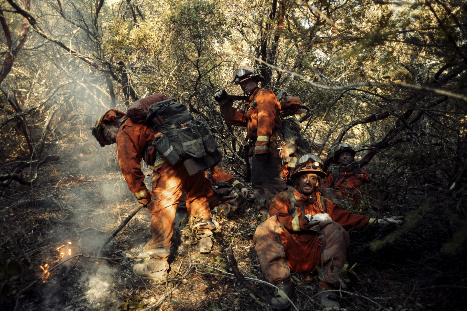 Inmate firefighters Eduardo Amezcua puts out a hotspot while Jon Hooker (standing with chainsaw) looks on during the fires that devastated much of California's wine country.