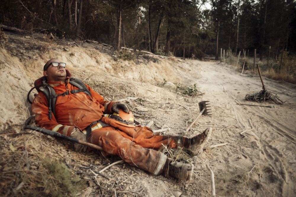 Eduardo Amezcua, an inmate fireman, exhausted from fighting wildfire in Sonoma, Ca, takes a break on the side of a fire trail.