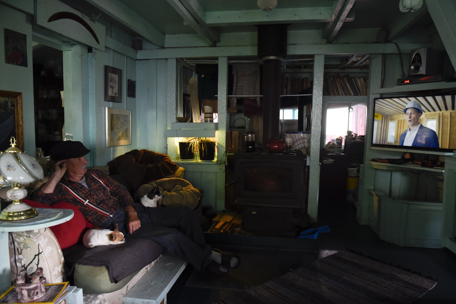 "Wayne Adams watches television with his dogs Joy and Huckleberry. The floating home, fully equipped with electricity from solar panels and a generator, has satellite internet and television. Adams, who is 68, constantly works to maintain the floating home. ""It's steady work,"" Adams said. ""These days I have to take breaks."""