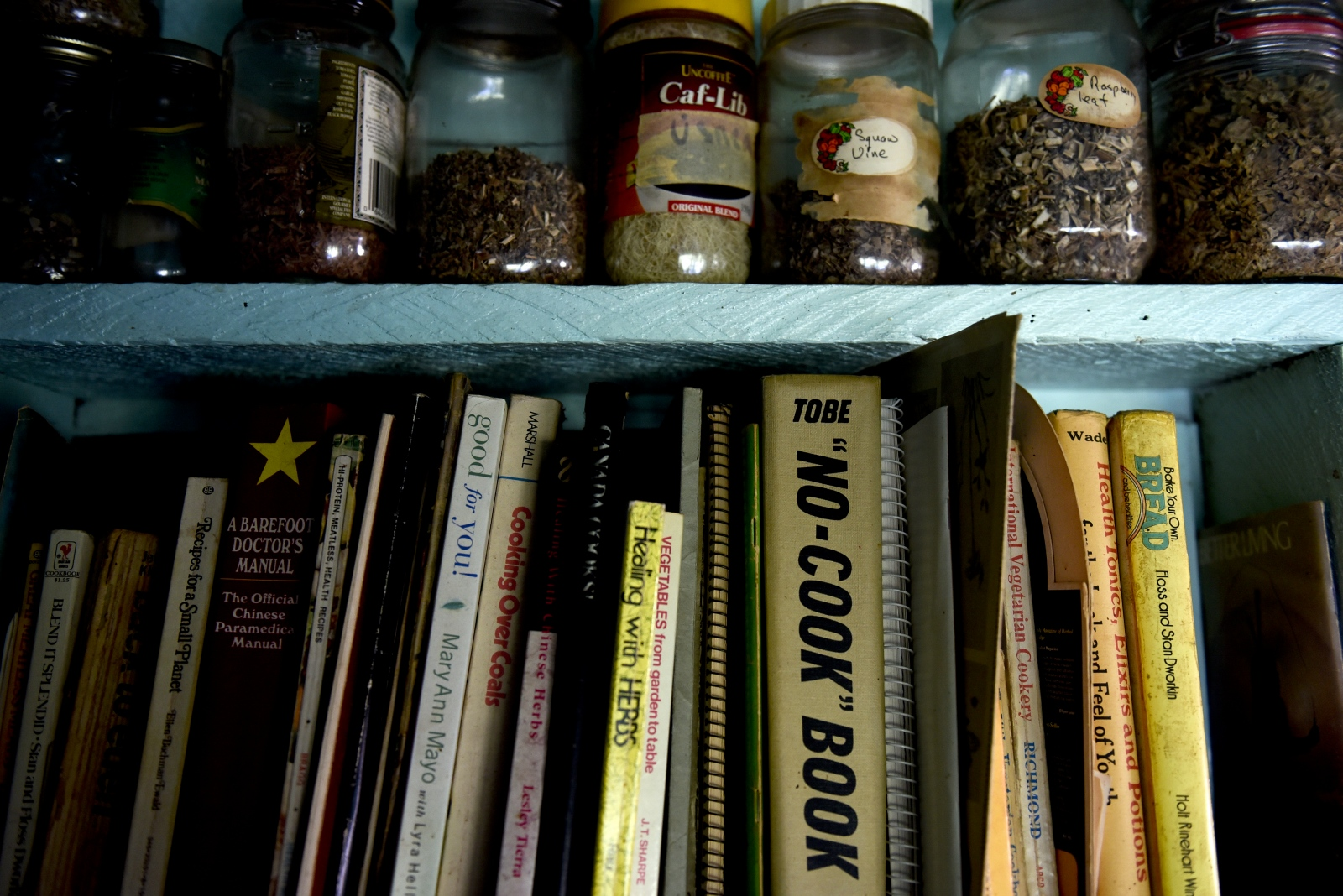 Spices and cookbooks are seen in the kitchen.