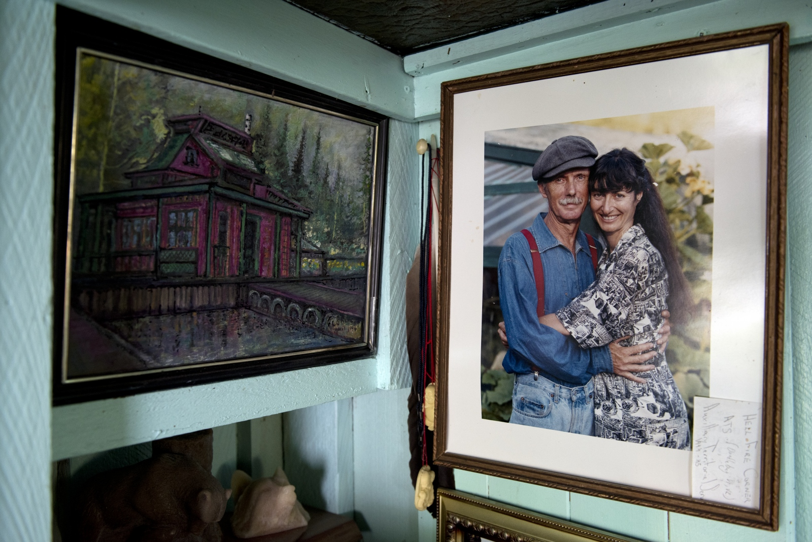 A portrait of Wayne Adams and Catherine King is seen next to a painting of their floating home in the home's living room. Adams and King met on Lasqueti Island, B.C., in 1987, and have been together since.