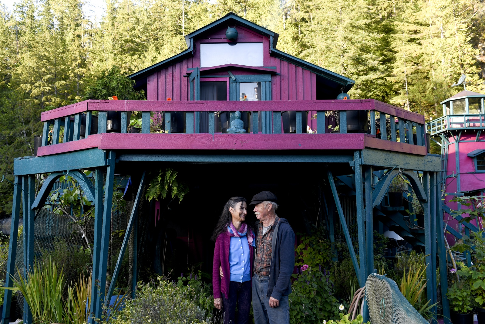 "Catherine King and Wayne Adams in their garden. The couple built and moved out to Freedom Cove in 1991. Adams and King insist their decision to move out into the wilderness did not come from a desire to isolate themselves. ""Pure economics,"" Adams said. ""As artists, we couldn't afford Tofino, Victoria or anywhere."" The couple describes their home as an art installation, open for the public to visit. ""It's an art piece meant to be walked through,"" King said. ""We like to share it because we want to encourage people to follow their own dream, whatever that is."""