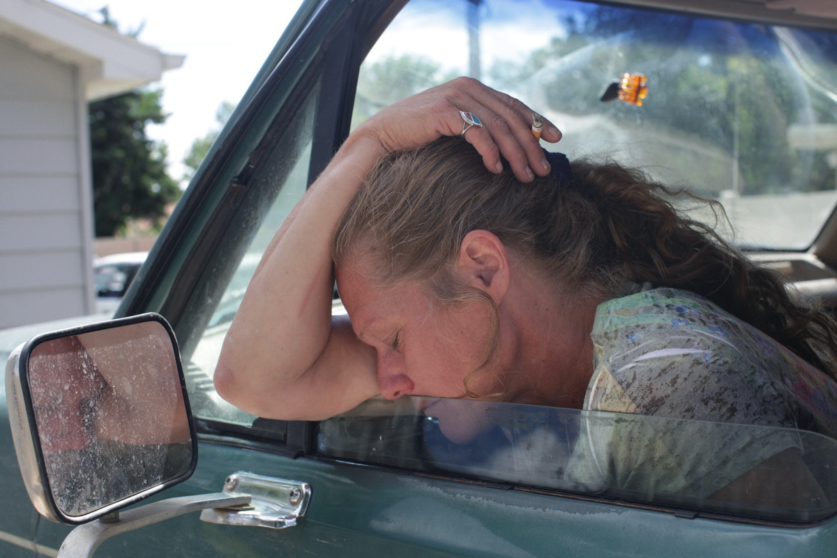 """You know what's nice?"" Charlotte asked, ""Being able to get in the car and go to the store...without asking."" Here, Charlotte rests in her car, outside a shelter in Williston, North Dakota on August 26, 2013. Charlotte moved to Williston that winter to seek work with her ex-boyfriend. After he held an unloaded gun to her head and stranded her in a parking lot with only their Ford Bronco, she began staying in her car until she found respite at the local shelter."