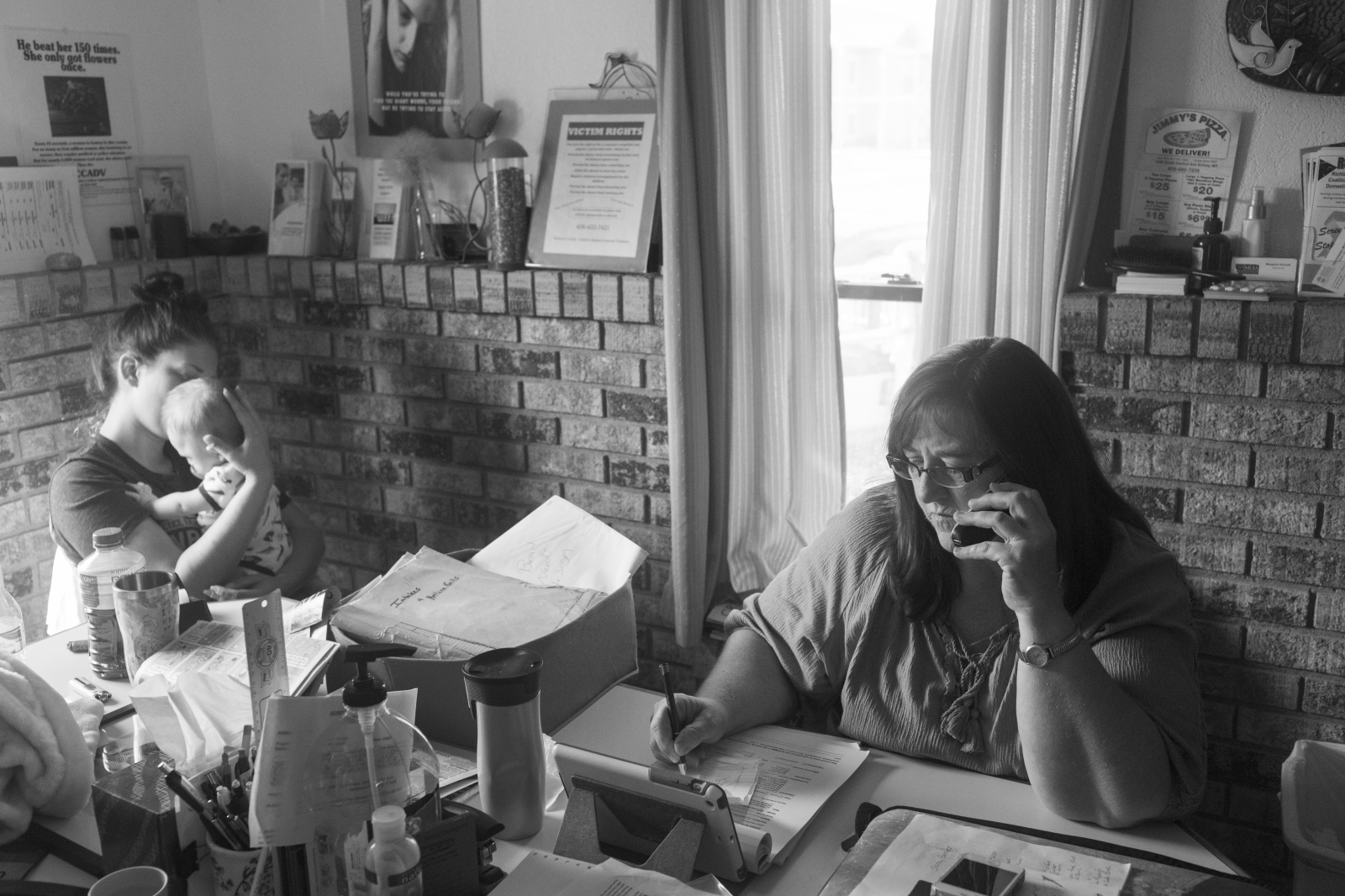 Rural areas have specific challenges regarding accessing support in cases of intimate partner violence. These challenges include high poverty, lower rates of health insurance coverage, and less access to healthcare and human services providers. Here, Helen answers calls, while another advocate takes care of a child while at work at a crisis center in rural Montana. Helen was Shirley's advocate and would consistently check in on her and drive her to most of her doctor appointments. Some appointments were over 4 hours away.